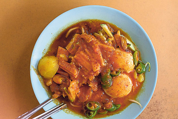 Abdul Rahim's mee kahwin is an inspired pairing of mee rebus and rojak — blanched yellow noodles are topped with taukua (fried beancurd), hard-boiled egg, potato cubes, fresh bean sprouts, crunchy cucur udang (prawn fritters), and cut green chillies.