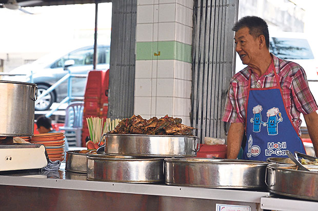 The affable proprietor of the Teochew porridge stall has a smile and greeting for every customer.