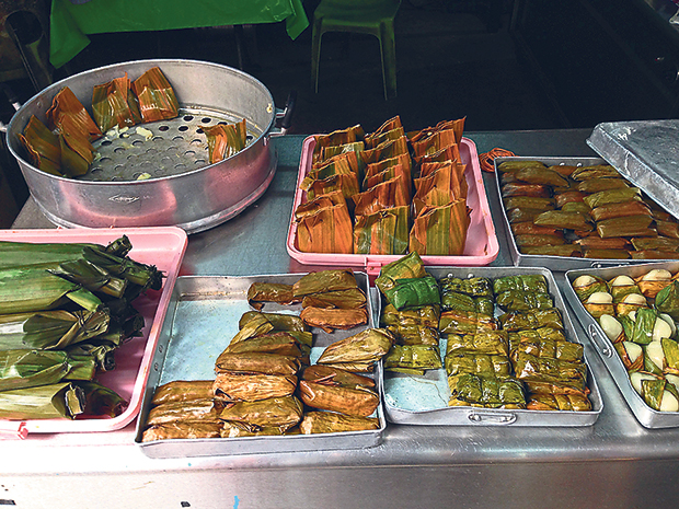 A selection of steamed kuih, all wrapped in banana leaves in various styles, at the cooked section of Pasar Chow Kit