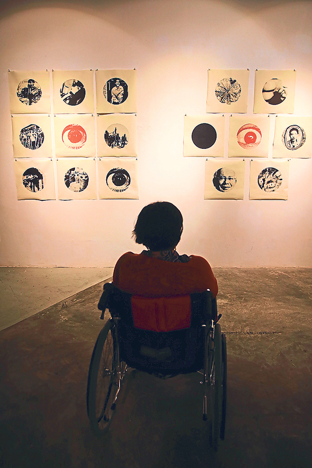 A visitor admiring local printmaker Poodien's work at Segaris Art Center by UiTM