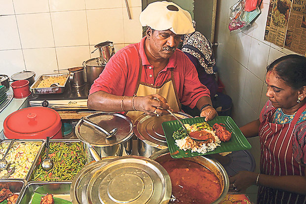 Scooping the food for the lunch sets at Panir Selvam's stall.