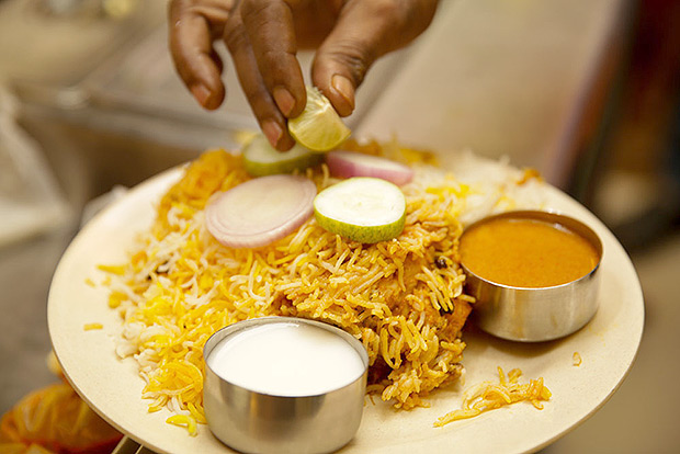 Adding a piece of cut lime to the biryani served at A P Bhavan.