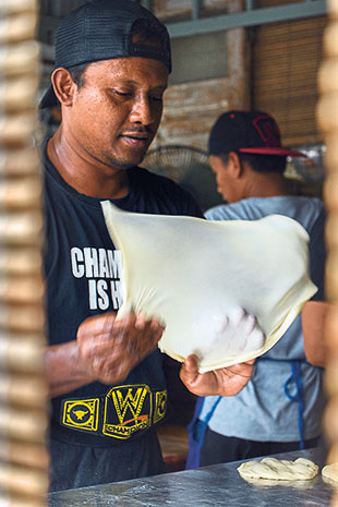 Flipping the dough for the roti canai to create more air pockets.