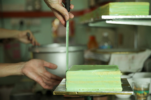It takes a deft hand to lay the special filling over the cake before it coagulates.