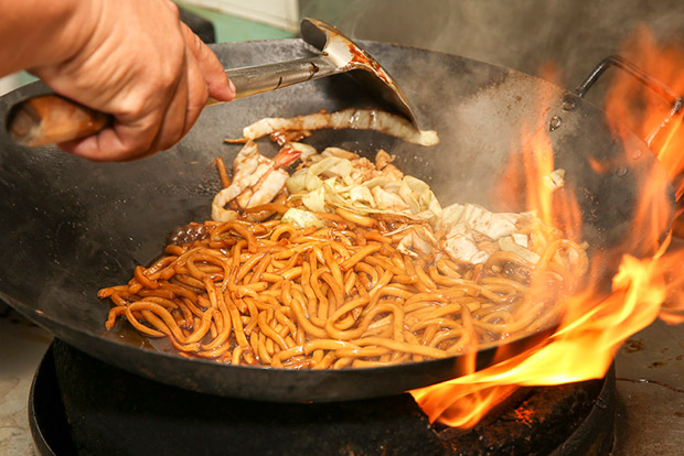 Frying the noodles require skills to handle the heavy wok and strong fire.