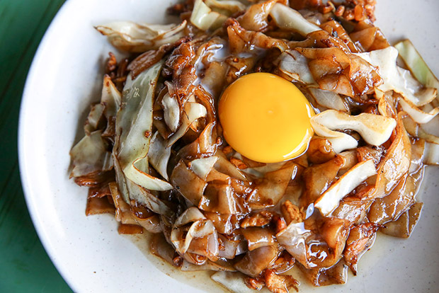 The kuey teow bulan has a raw egg cracked over the fried noodles.
