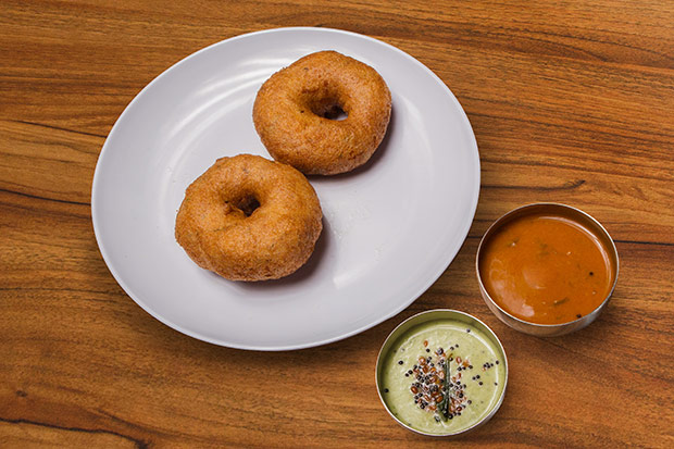 Snack on these fluffy uddin vada or fried lentil doughnuts with chutney and sambar.