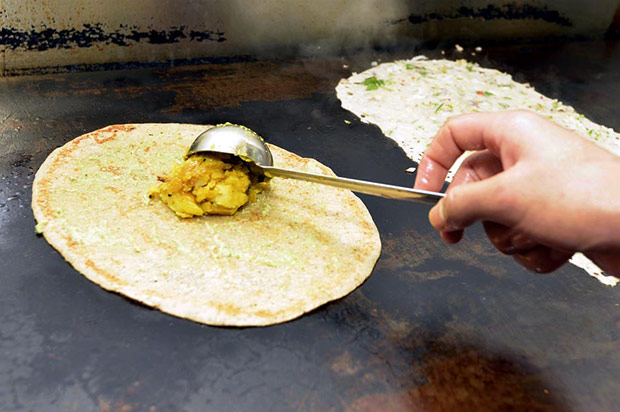 A spiced potato filling is added on top of the half cooked dosa.