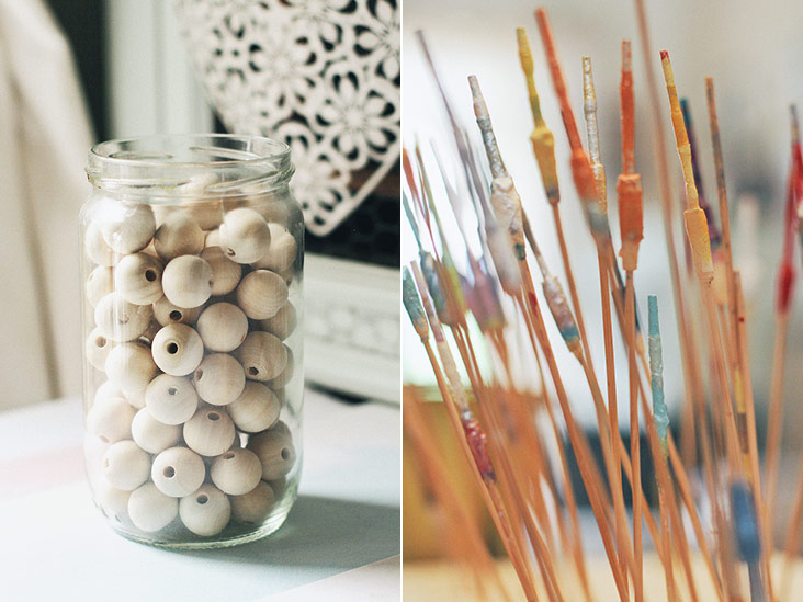 The humble wooden bead is light weight and given a new lease of life with a coat of paint and varnish (left). Wooden sticks are used to prop and allow the beads to dry overnight after they are painted (right).