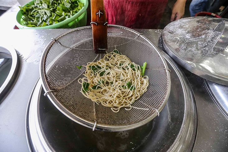 Once the noodles are ready, they will be ladled out and drained first.