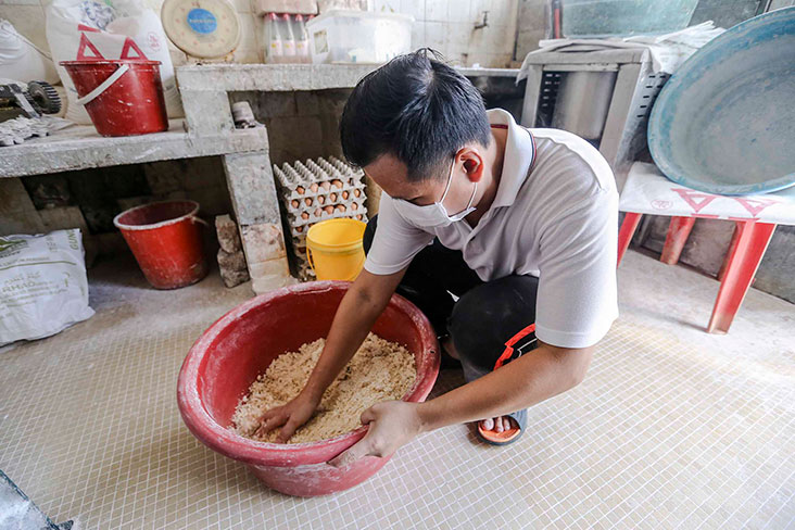 The dough for the noodles is shaken and loosened up before it is placed in the machine to flatten.