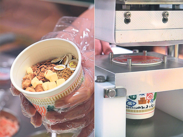 Mix-and-match and fill your cups — there is no flavour combination that's too weird (left). A machine covers your customised cup with a signature Nissin cup noodles lid (right)