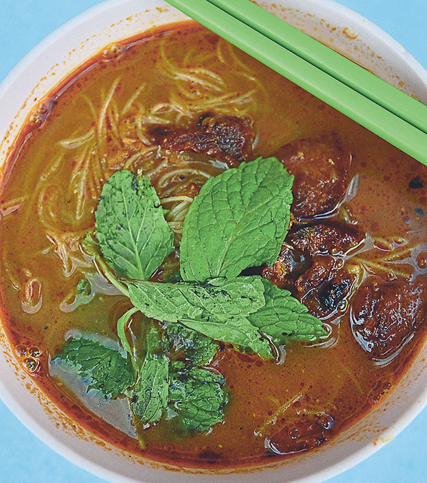 A bowl of curry noodles at Foo Kwai, with slices of their homemade char siew and garnished with fresh mint leaves. – Pictures by James Tan