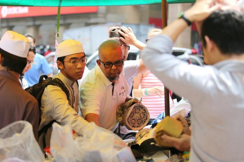 Men buying/trying out some kopiah outside Masjid Jamek, near Jalan Tunku Abdul Rahman. – Picture by Choo Choy May