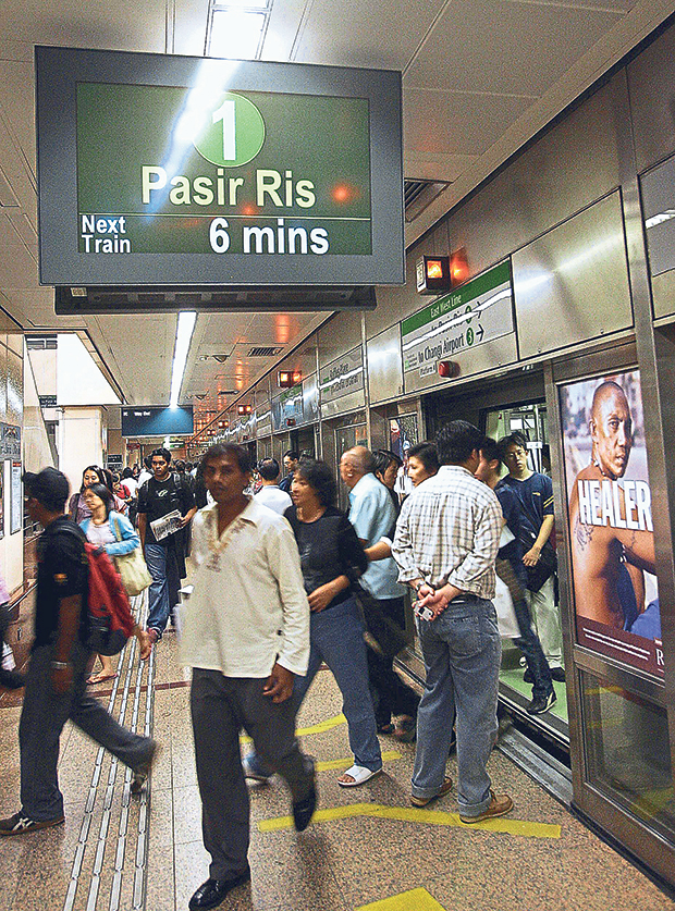 Commuters exit and enter a subway train at the Raffles Place Mass Rapit Transport station in Singapore. — Picture from AFP