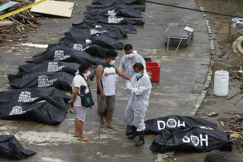 A man points at one of the bags containing bodies of typhoon victims in Tacloban city, which was devastated by Typhoon Haiyan, in central Philippines November 12, 2013. Relief efforts are intensifying with the help of the US military. — Reuters pic