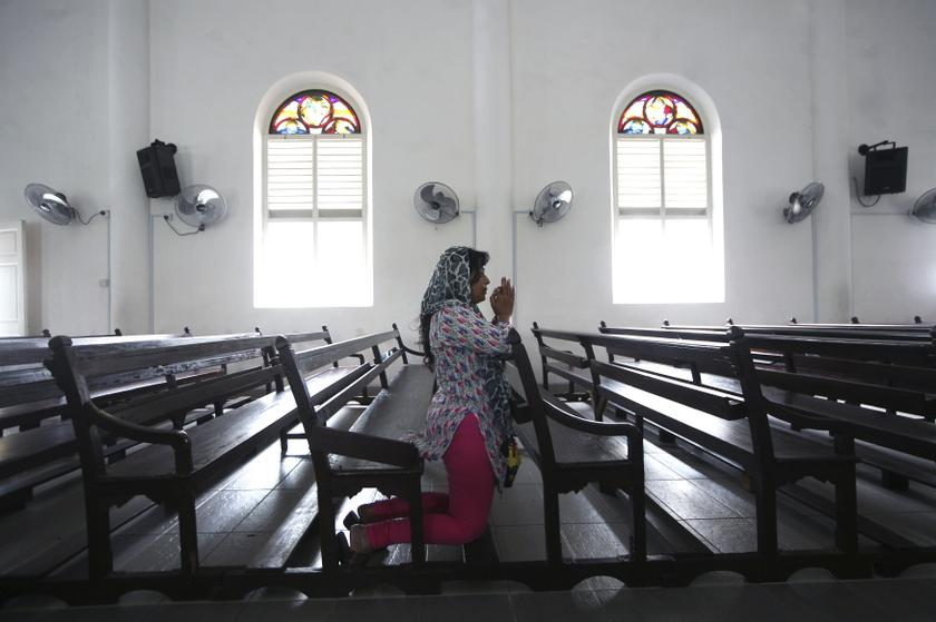 A file picture of a woman praying inside the church of Our Lady of Lourdes in Klang. A group of Taman Medan residents staged a peaceful protest against a new church in fearing proselytization after the church's congregation had put up a cross on the building. — Reuters pic