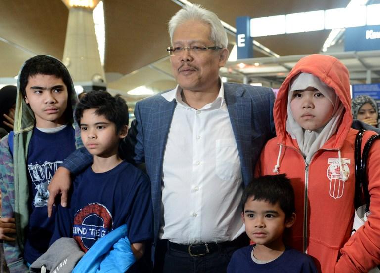 Children of Malaysian Muslim couple Azizul Raheem Awalludin and his wife Shalwati Nurshal with Malaysian Deputy Foreign Minister Datuk Hamzah Zainuddin  after they arrived at Kuala Lumpur on February 1, 2014. — AFP pic