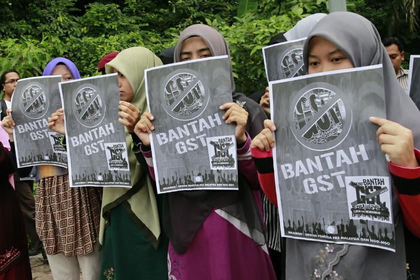 Participants of an anti-GST rally holding banners in front of Parliament before the tabling of Budget 2014 in Kuala Lumpur, October 25, 2013. — Picture by Saw Siow Feng
