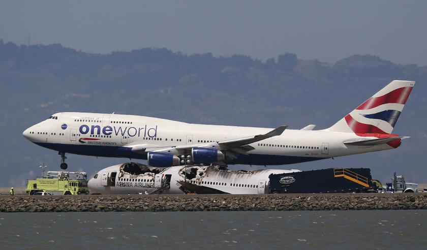 A British Airways Oneworld jumbo jet lands near the charred remains of Asiana Airlines Flight 214 on the runway at San Francisco Airport International Airport in San Francisco, California July 9, 2013. — Reuters pic