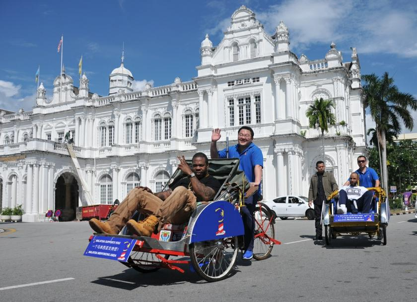 Low (centre) pedals a trishaw carrying US rapper Busta Rhymes in George Town April 19, 2013. — Picture by KE Ooi