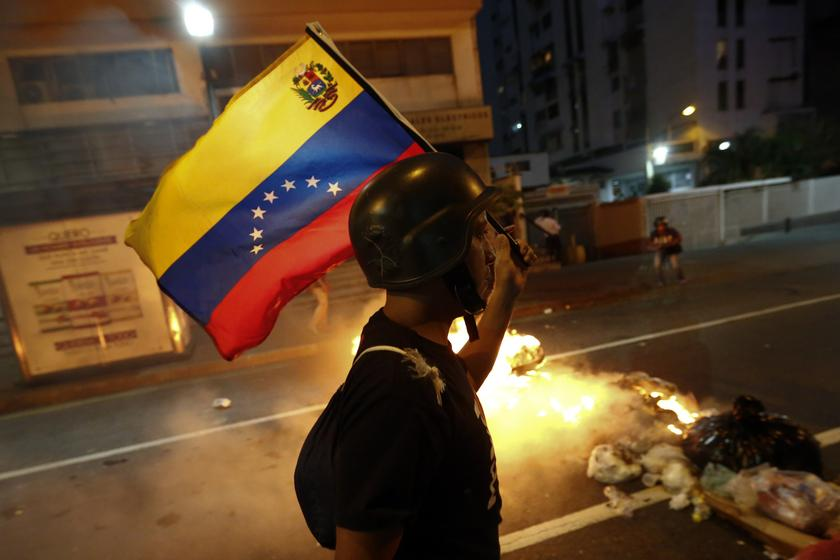 An opposition demonstrator carries a Venezuelan flag as he walks past a burning barricade during a protest in Caracas February 12, 2014. — Reuters pic