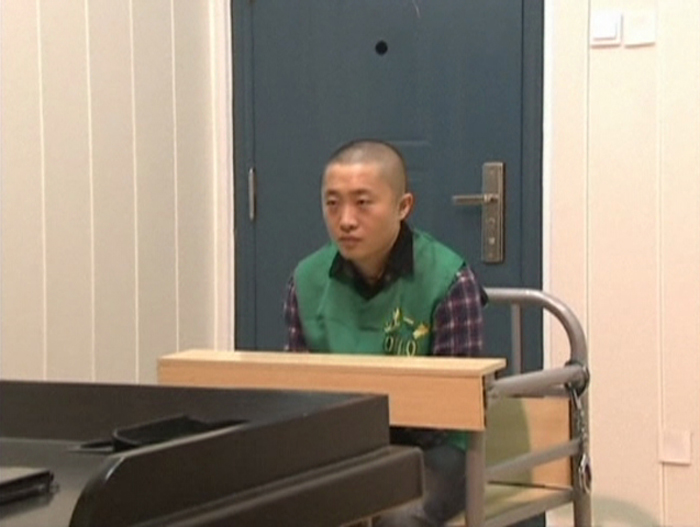 Journalist Chen Yongzhou sits in a detention room at the Changsha Public Security Bureau detention centre in Changsha City, Hunan Province, in this still image taken from China Central Television (CCTV) video shot on October 25, 2013. — Reuters pic