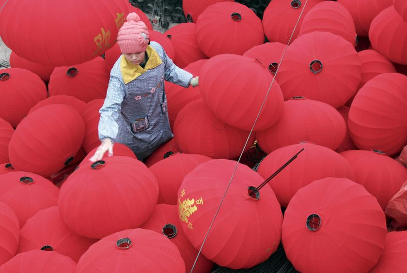 A worker walks among newly-made red lanterns as she and other workers prepare for the sales boom ahead of the Spring Festival at a family workshop in Wenxian county, Henan province January 7, 2014. — Reuters pic