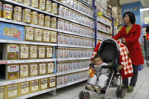A woman looks at baby milk powder in a supermarket in Nanjing, east China's Jiangsu province on March 29, 2013. — AFP pic