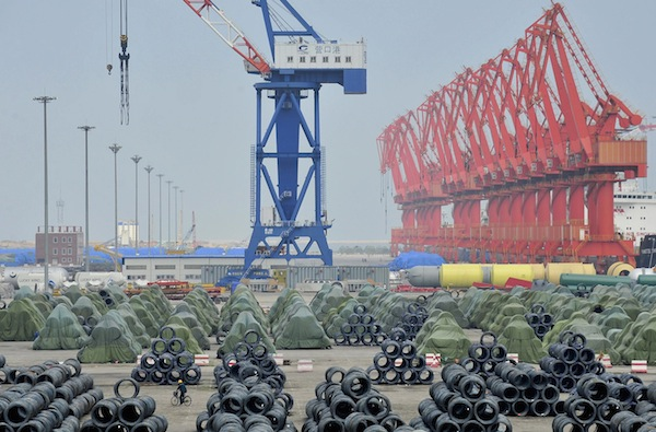 A worker rides his bicycle past piles of steel coils for export at a port in Yingkou, Liaoning province August 9, 2013. — Reuters pic