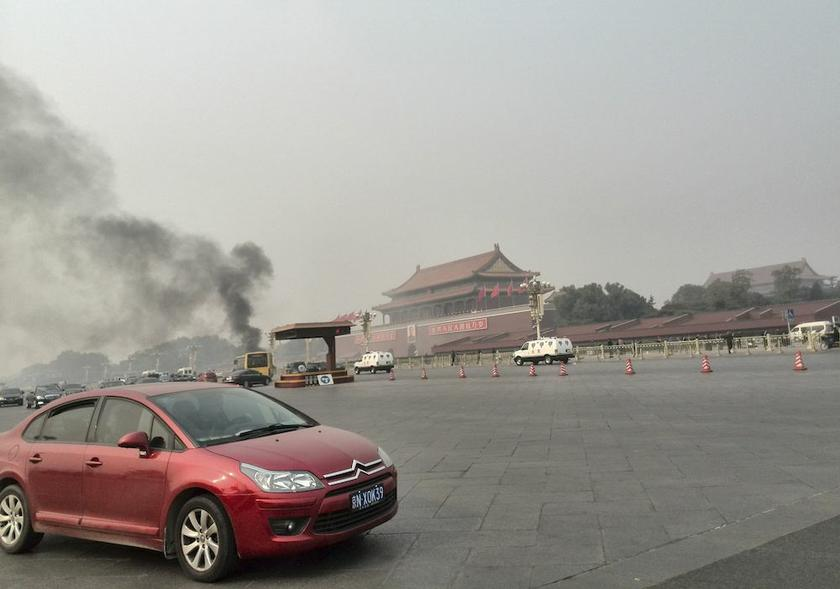 Vehicles travel along Chang'an Avenue as smoke raises in front of a portrait of late Chinese Chairman Mao Zedong after a car accident at Tiananmen Square in Beijing October 28, 2013. — Reuters pic