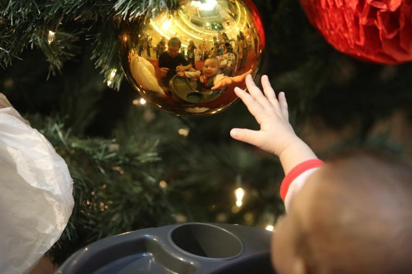 A baby trying to grab a hold of a Christmas decorative bauble hanging from a Christmas tree at Mid Valley Megalmall in Kuala Lumpur, December 24, 2013. — Picture by Choo Choy May