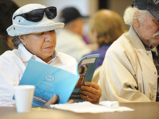 A retiree reads a pamphlet this month advising elderly people how to avoid fraud and scams in South Gate, Calif. — AFP pic