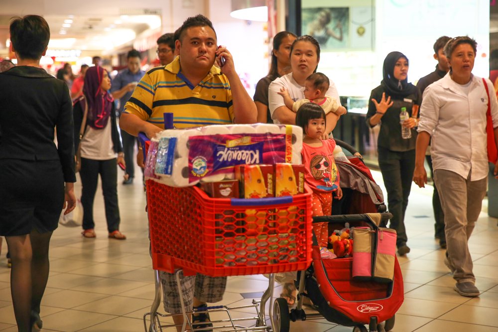 A family push a cart to their car after buying groceries at a hypermarket in a shopping mall in Kuala Lumpur. — Picture by Saw Siow Feng