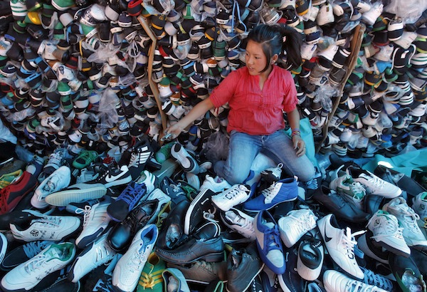 A roadside vendor sells a pair of shoes on a street in Srinagar September 9, 2013. — Reuters pic