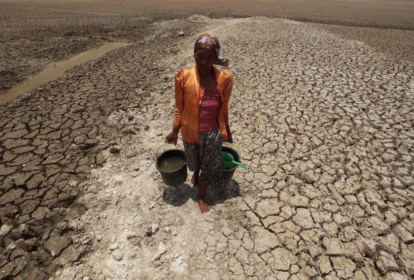 A female villager walks after collecting water from the base of a dried-up reservoir, due to the long dry season, at Kedung Sumber village, near Bojonegoro in Indonesia's East Java province, October 16, 2013. — Reuters pic