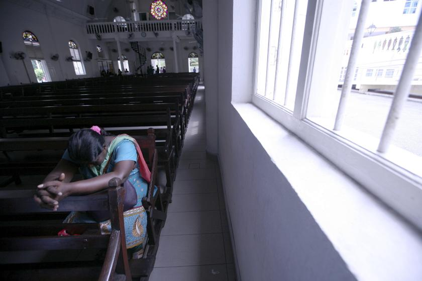 A woman prays inside the church of Our Lady of Lourdes at Klang, outside Kuala Lumpur January 12, 2014. — Reuters pic