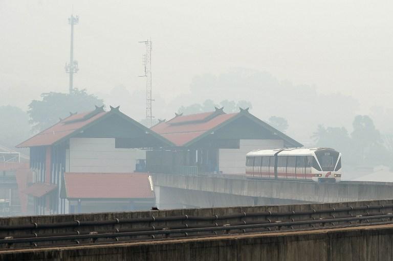 A Light Rail Transit (LRT) train travels along its tracks in Kuala Lumpur as haze covers the city on June 23, 2013. The Kelana Jaya-Ampang LRT line extension will start operating on Thursday, Prasarana said today. — AFP pic