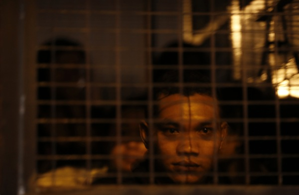 File picture of a detained suspected illegal migrant worker in an immigration truck during a crackdown. Datuk Wan Junaidi Tuanku Jaafar said said stringent measures must be taken to keep the east Malaysian state clean of illegals, including immediate deportation of those caught without valid travel documents. — Reuters pic
