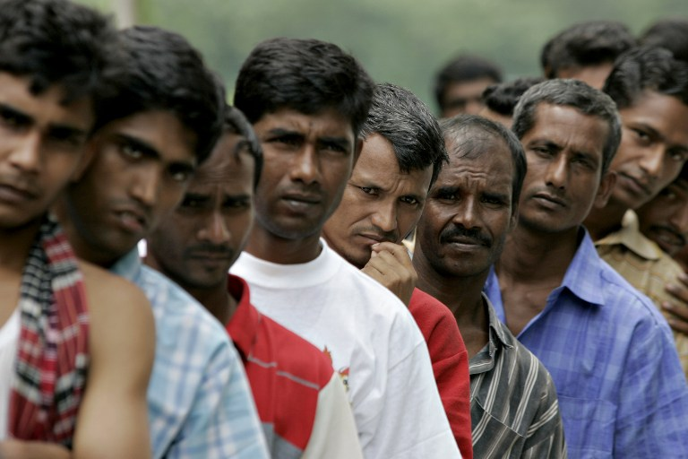 This file photo taken on December 25, 2007 shows Bangladeshi workers waiting in line for food donated by a goodwill charity group for Christmas outside the Bangladeshi High Commission in Kuala Lumpur. — AFP pic