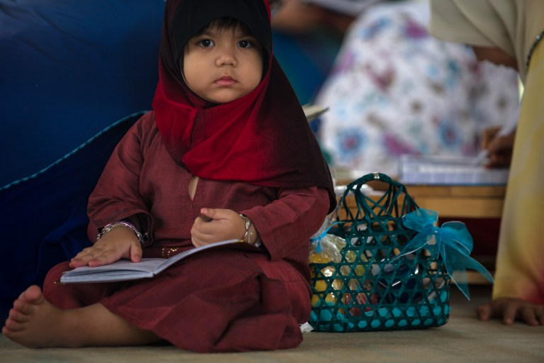 A young Muslim girl waits for her mother inside a mosque during Al-Quran recital and graduation ceremony in Putrajaya, outside Kuala Lumpur on August 1, 2013. — AFP pic