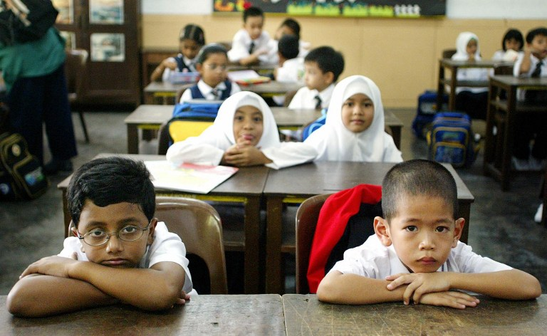 Children attend their first day of elementary school in Standard One (Primary One) at a local school on the start of the new school year in Kuala Lumpur 06 January 2003. — AFP pic