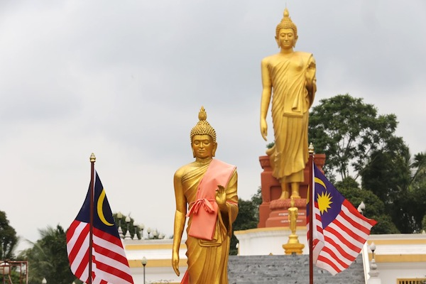 """A smaller Buddha statue in Wat Pikulthong with the iconic giant Standing Buddha, or """"Buddhalila"""", statue in the background."""