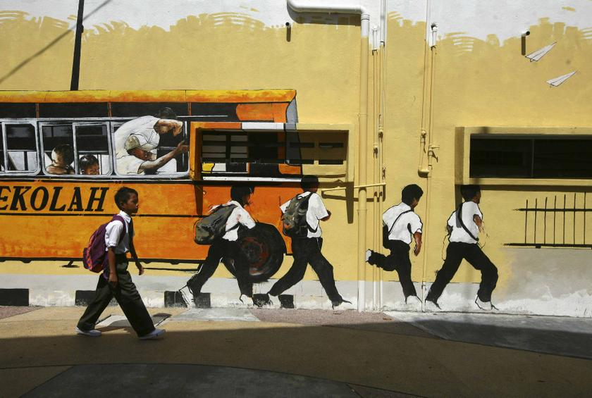 A school boy walks past a street mural depicting a school bus and students in Shah Alam January 2, 2014. — Reuters pic