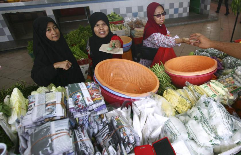 Women pay their bills at a wet market in Shah Alam outside Kuala Lumpur January 22, 2014. — Reuters pic