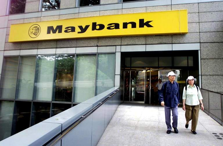 A couple walks out from a branch of the Malayan Banking Bhd (Maybank), Malaysia's biggest bank, in Kuala Lumpur's financial district, on September 27, 2001. — AFP pic