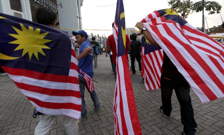 Malaysians hold national flags during a rally to celebrate the country's 55th Independence Day in Bukit Jalil Stadium August 31, 2012. The bloody May 13 racial riots of 1969 should be a lesson for the multiracial people in the country to recognise the importance of staying united in order to maintain peace and live in harmony. — AFP pic