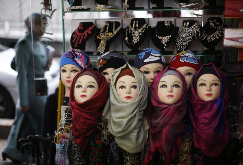 A Palestinian woman walks past a shop selling head scarves in the West Bank city of Ramallah December 4, 2013. — Reuters pic