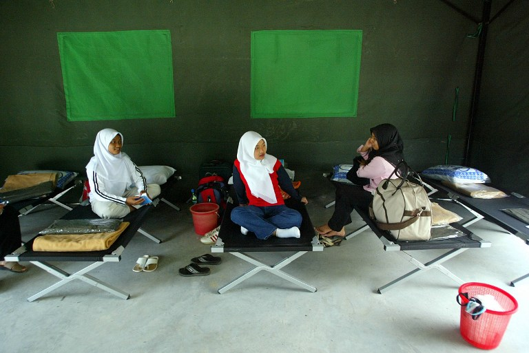 Female students sit in their tent on the first day of the National Service Program at a camp in Kuala Kubu Baru outside of Kuala Lumpur 16 February 2004. —AFP pic