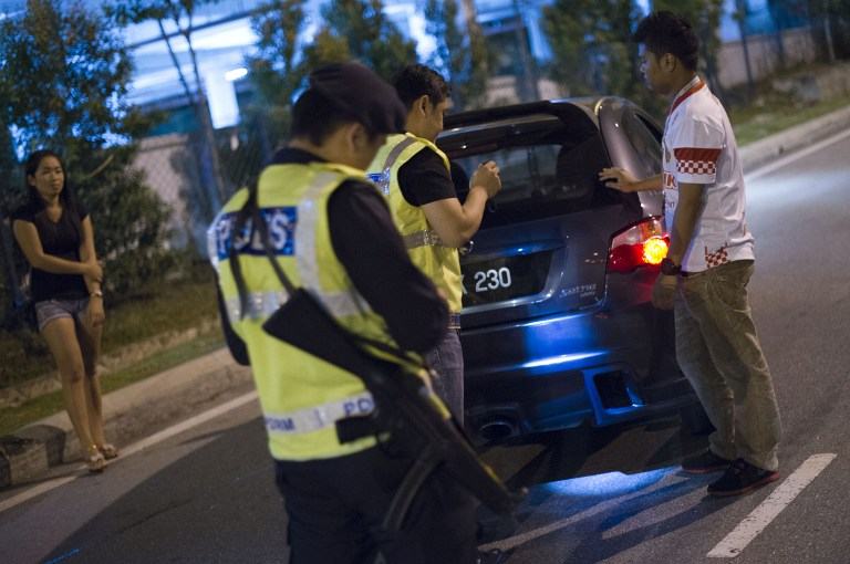 The High Court was told today that single mother Norizan Salleh's claim that she was shot five times by the police five years ago was not investigated despite a police report lodge on the matter. This picture taken in the early hours of August 21, 2013 shows Malaysian policemen checking a vehicle at a roadblock in Kuala Lumpur. — AFP pic